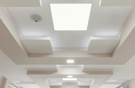 A series of flat panel LED lights are shown surface mounted to the ceiling of a boutique retail store, illustrating how their sleek low profile perfectly blends in with high end interior design