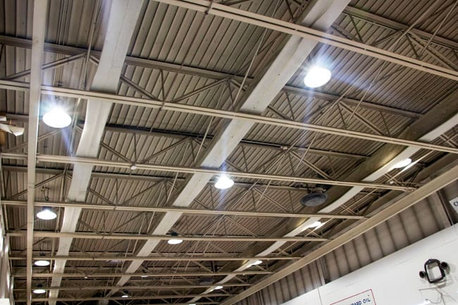 Round UFO high bay fixtures projecting bright illumination from the ceiling of an industrial facility