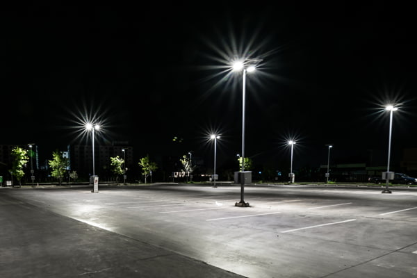 An empty parking lot being lit by LED light poles