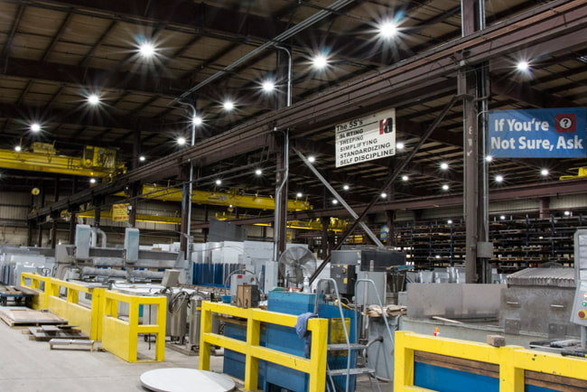 A large metal manufacturing facility is shown with multiple LED high bay lights suspended above providing intense illumination to the shop floor and heavy equipment below